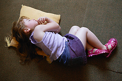 Young girl sleeping on the carpet,