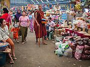 07 MARCH 2014 - MAE SOT, TAK, THAILAND: A Burmese Buddhist monk walks through the market in Mae Sot, Thailand.     PHOTO BY JACK KURTZ