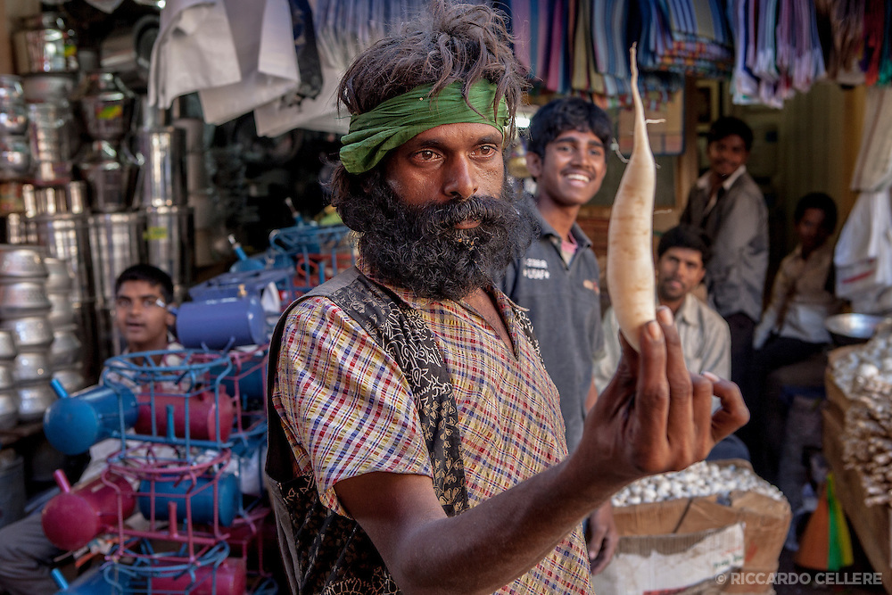 This whimsical gentleman was enthusiastic about being photographed, but insisted on holding various vegetables right in front of his face. City Market, Bangalore, India
