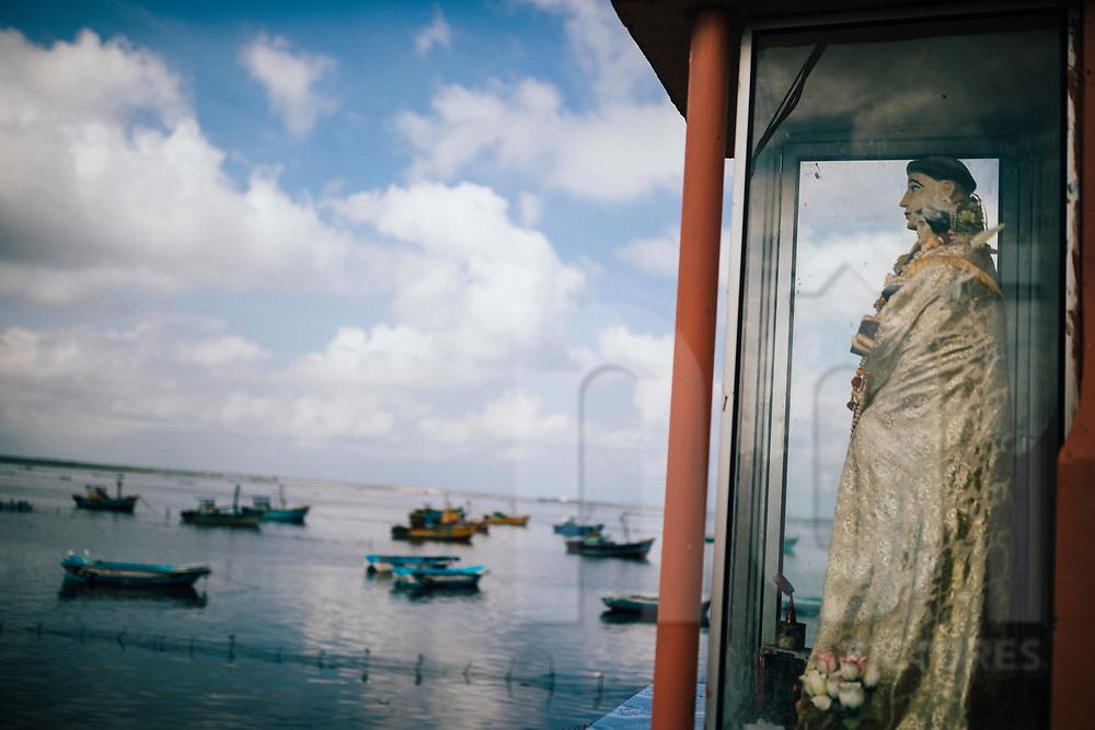 A statue of a saint watches over fishermen boats in Jaffna, Sri Lanka, Asia