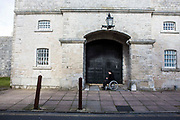The wife of a prisoner waiting outside the prison gate to see her husband on a visit. HMP/YOI Portland, Dorset. A resettlement prison with a capacity for 530 prisoners. Portland, Dorset, United Kingdom.