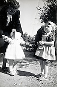 grandmother holding a toddler with sister standing by France 1950s 1960s