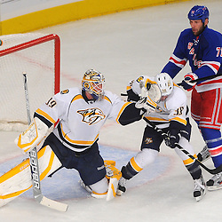 Nashville Predators goalie Anders Lindback (39) catches a shot in his catching glove as it nears impact with defenseman Jack Hillen's (38) helmet with New York Rangers left wing Mike Rupp (71) applying pressure during first period NHL action between the New York Rangers and the Nashville Predators at Madison Square Garden in New York, NY. The Rangers lead the Predators 1-0 at the first intermission.