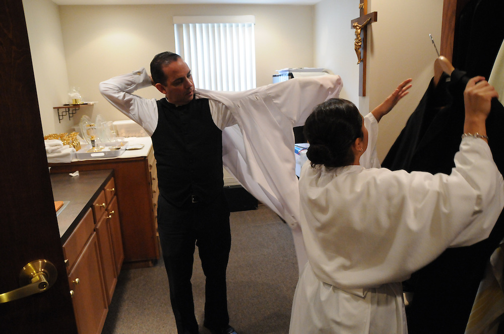 Father Claudio Diaz Jr. prepares his vestments before his official installation mass as Pastor of Mision San Juan Diego in Arlington Heights.