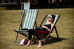 © Licensed to London News Pictures. 16/07/2019. LONDON, UK.  A woman relaxes on a deckchair in the sunshine in St. James's Park.  Temperatures are forecast to rise to 26C.  Photo credit: Stephen Chung/LNP