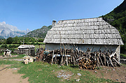 A stone farm house with a traditional shingled roof in the community of Teth. Firewood for the winter is piled up under the eaves.Teth, Tethi, Albania. 03Sep15