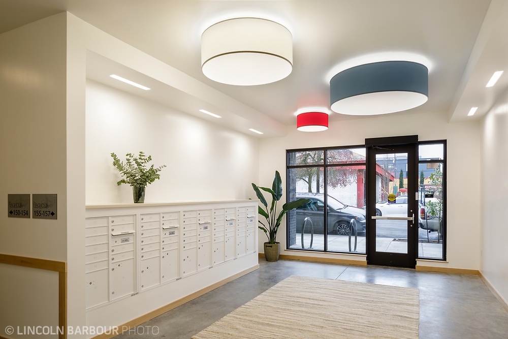 The lobby of an affordable housing apartment building with mailboxes along the left hand wall.  Modern light fixtures over head.