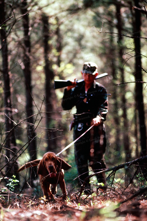 """James Phelps with bloodhound, Mac on the lookout for odors of shoes, sweat, crushed vegetation. James says, """"only Mac knows what odor he follows.""""<br /> <br /> James Phelps is lead by his bloodhound Mac.  Phelps uses his dog to track prison escapees in Georgia."""