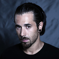 urban stylish caucasian young man with pierced ears and piercing studio portrait