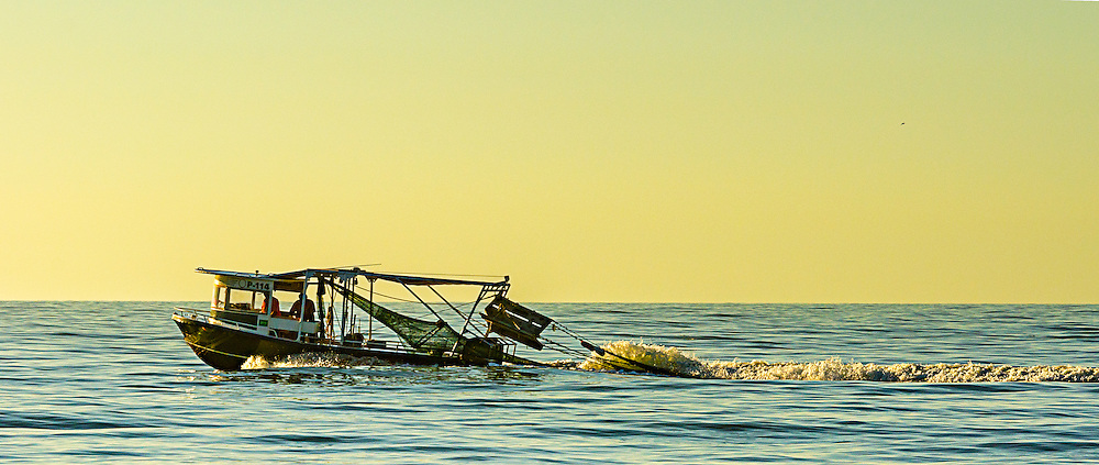 It was an early morning on the beach when this boat went by.  I love what the light did to the sky