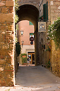 A tourist walks his bicycle through the streets of Pienza, Italy. (between Rome and Florence, near Montepulciano).