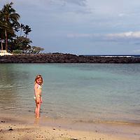 USA, Hawaii, Honolulu. Young girl on private beach at The Kahala Resort.