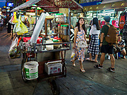 24 JULY 2018 - BANGKOK, THAILAND:  A coffee vender pushes his cart past a tourist up Khao San Road in Bangkok. Khao San Road is Bangkok's original backpacker district and is still a popular hub for travelers, with an active night market and many street food stalls. The Bangkok municipal government plans to shut down the street market by early August because city officials say the venders, who set up on sidewalks and public streets, pose a threat to public safety and could impede emergency vehicles. It's the latest in a series of night markets and street markets the city has closed.  PHOTO BY JACK KURTZ