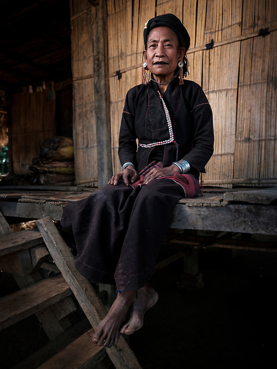 KYAING TONG, MYANMAR - CIRCA DECEMBER 2017: Portrait of a woman at the Bam Kin Mai Eng seating outside her home. The Eng tribe are known for their black teeth. They believe black teeth are attractive and chew tree bark and beetle nut to darken them.<br /> Kyaing Tong