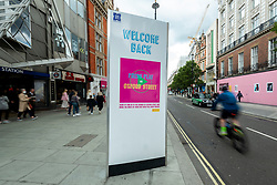 © Licensed to London News Pictures. 26/05/2021. LONDON, UK.  People pass a Welcome Back sign on Oxford Street as retailers hope that the easing of lockdown results in increased store sales as evidence of pent-up demand from shoppers.  Photo credit: Stephen Chung/LNP