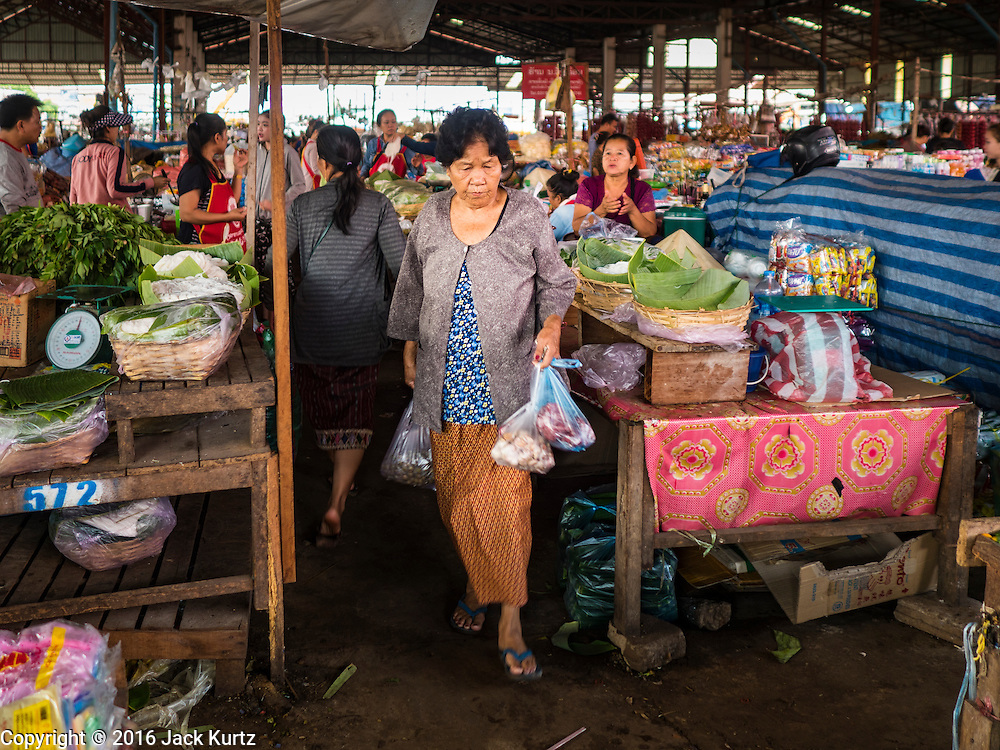 16 JUNE 2016 - PAKSE, CHAMPASAK, LAOS: A woman walks through Dao Heuang Market, the largest market in Pakse. Pakse is the capital of Champasak province in southern Laos. It sits at the confluence of the Xe Don and Mekong Rivers. It's the gateway city to 4,000 Islands, near the border of Cambodia and the coffee growing highlands of southern Laos.      PHOTO BY JACK KURTZ