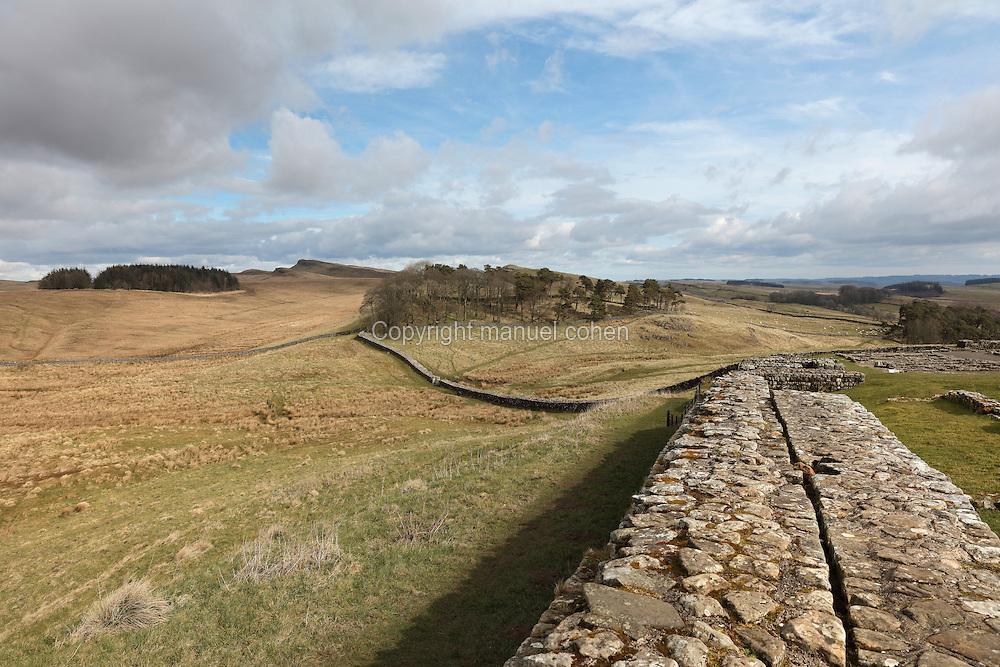 Housesteads Roman Fort (right), built in 124 AD, and Hadrian's Wall looking East, Northumberland, England. Housesteads is the most complete Roman fort in Britain, built by legionaries to house 10 centuries of auxiliary soldiers based on the frontier. Hadrian's Wall was built 73 miles across Britannia, now England, 122-128 AD, under the reign of Emperor Hadrian, ruled 117-138, to mark the Northern extent of the Roman Empire and guard against barbarian attacks from the Picts to the North. The wall was fortified with milecastles with 2 turrets in between, and a fort about every 5 Roman miles. This section of the Wall is in the Northumberland National Park, managed by the National Trust, and the Hadrian's Wall Path, an 84-mile coast to coast long distance footpath, runs alongside it. Picture by Manuel Cohen