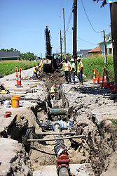 26 August 2015. New Orleans, Louisiana. <br /> Hurricane Katrina revisited. <br /> Rebuilding the Lower 9th Ward. <br /> Contractors working on behalf of the New Orleans Sewerage and Water Board repair supply pipes and drains providing hope for the rebirth of the community following the devastation of hurricane Katrina a decade earlier.<br /> Photo credit©; Charlie Varley/varleypix.com.