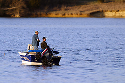 09 April 2005:   A pair of fishermen navigate the waters of a lake in a fishing boat with an outboard motor in search of a catch.