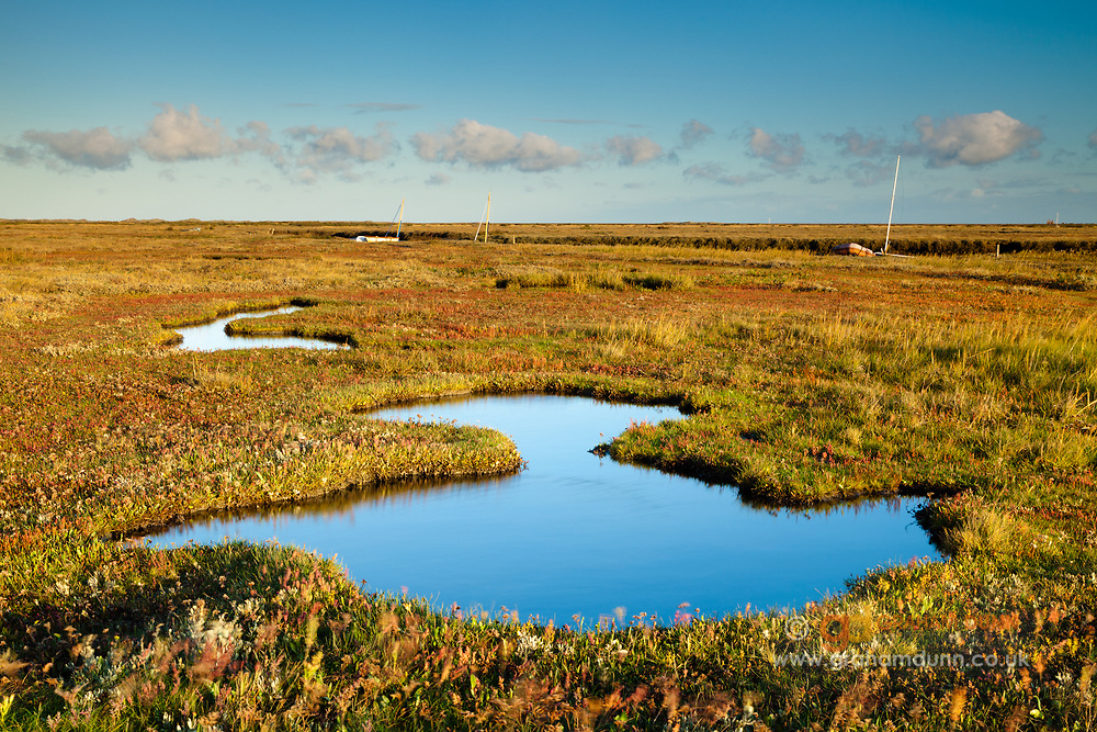 Salt marsh pools reflect the morning sky at Blakeney, North Norfolk, East Anglia.