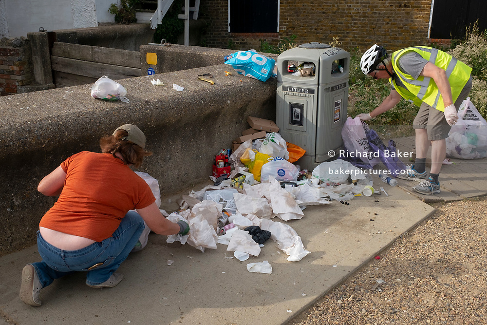 The morning after Saturday night crowds of young peoples' nightlife beach parties, their litter and rubbish from the night before stretches across the coastal paths and shingle, local volunteers pick up and bags up piles of litter along the sea wall, on 19th July 2020, in Whitstable, Kent, England.  The volunteers and a council cleaner come every morning to clean-up the mess left by others which, they say, has got worse during the Coronavirus pandemic lockdown and now, the slow easing of health guidelines.