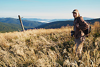 """Kamil Soos (NGO """"Wolf"""") hiking on the borderland trail between Poland (in the background) and Slovakia on the peak of Mount Durkovec (1189m), Runina area, Slovakia."""
