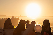 Silhouettes of tourists enjoying sea view at sunset, Casablanca, Morocco
