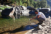 hiker rests by a stream at Yosemite national Park, California USA
