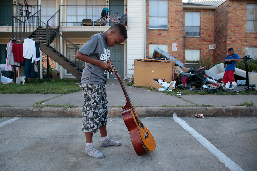 Jacob Chaisson, 9, left, and his brother Joseph Chaisson, 10, plays with items that they found in the piles of destroyed property at Crofton Place Apartments in the aftermath of Hurricane Harvey in Houston, Texas, U.S. September 8, 2017.