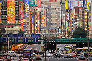 Pedestrian, car, bus, and train traffic at a busy intersection in the Shinjuku District of Tokyo, Japan.