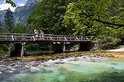 A family look at the view of the Savica river at Ucanc from a wooden bridge near Lake Bohinj, on 19th June, in Lake Bohinj, Sovenia