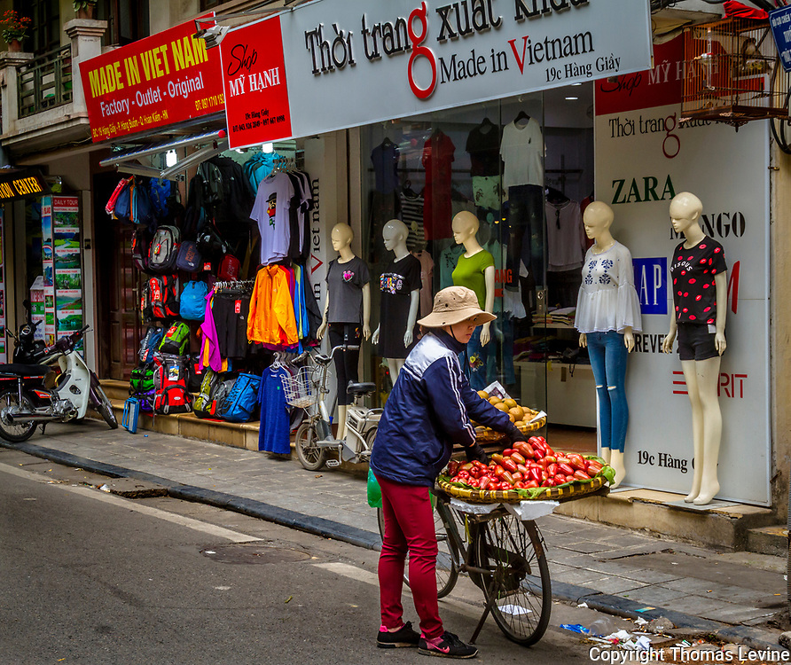 Old Quarter, Hanoi, Vietnam, 3/27/17, Street fruit vendor lady in front of clothing shop with mannequins.