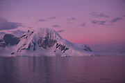 Antarctic Peninsula after summer sunset at 11:35 PM. Because in summer it does not get dark, there are several hours each day/night with pink skies. Seen from the Scandinavian-built ice-breaker Akademik Sergey Vavilov, originally built for the Russian Academy.