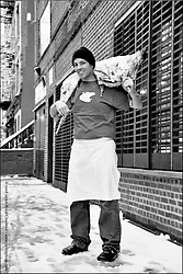 Steven Duane Cameron stands in front of dram bar for his lamb supper club with Peerless Platters in Williamsburg, Brooklyn, New York.  He holds the lamb from White Gate Farms, Connecticut.  Lovingly raised and slaughtered by its farmer.