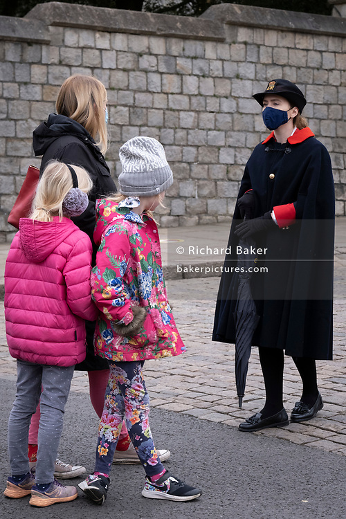 The day after the death at age 99 of Prince Phillip, the Duke of Edinburgh, consort to Queen Elizabeth II, a young member of the Royal Household directs members of the public outside Windsor Castle where the Queen has been isolating throughout the Coronavirus pandemic, on 10th April 2021, in London, England.