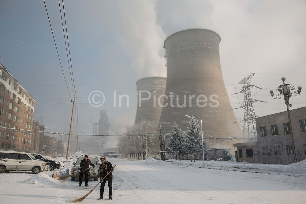 Residents sweep a snow covered street as water vapor and smoke rise from a Tonghua Iron & Steel Group Co. plant in the distance in the Erdaojiang district in Tonghua, Jilin province, China, on Wednesday, Jan. 6, 2016. The citys once-vaunted state-run steel mills have slipped inexorably into decline, weighed down by slumping global markets, a changing economy, and the burden of costs and responsibilities to the people of the town they fostered. Previous attempts to privatise the enterprise have met with stiff resistance, one such attempt resulted the mob lynching and death of a private businessman who wanted to invest and streamline the operation.