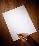 Man's hand poised over blank piece of paper preparing to write something