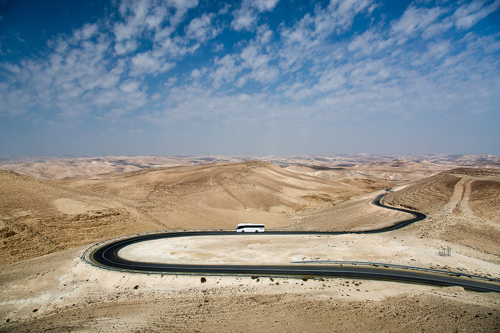 A tourist bus is traveling along a road in the Judean Desert