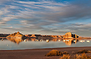 Sunset illuminates sandstone and houseboats at sunset on Lake Powell, which is impounded by Glen Canyon Dam on the Colorado River on the Utah and Arizona border, USA. Lake Powell is the second largest man-made reservoir in the United States. The reservoir is named for explorer John Wesley Powell, a one-armed American Civil War veteran who explored the river via three wooden boats in 1869. The dam generates electrical power, controls flooding, and provides water recreation, at the cost of various environmental changes.