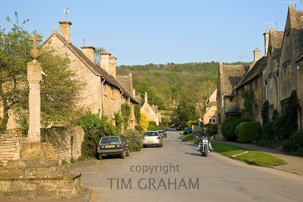Motorcyclist rides through Stanton village, Gloucestershire,  The Cotswolds, United Kingdom