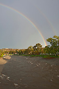 A double rainbow over storm water emptying from Storm Pipes into Ballona Creek, a nine-mile waterway that drains the Los Angeles basin. Urban runoff carries an assortment of trash and debris from catch basins where a network of pipes and open channels create a pathway to the Ocean at Santa Monica Bay. Ballona Creek is designed to discharge to Santa Monica Bay approximately 71,400 cubic feet per second from a 50-year frequency storm event. Culver City, Los Angeles, California, USA