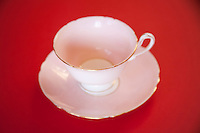 Pink china tea cup and saucer with gold trim on a red background