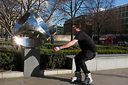 Inline skater practicing tricks by a sculpture along a wall in St Pauls London, UK.
