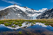 A tarn reflects glacier-clad Mt Edward and Dart Glacier on a 20 kilometer round trip hike to Cascade Saddle from Dart Hut, in Mount Aspiring National Park, Otago region, South Island of New Zealand.