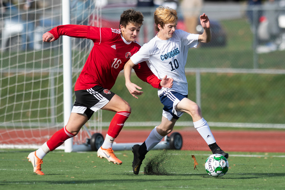 CVU's Sam Johnson (18) battles for the ball with Eddie Kane (10) during the DI boys soccer championship game between the Mount Mansfield Cougars and the Champlain Valley Union Redhawks at Buck Hard Field on Saturday morning November 2, 2019 in Burlington, Vermont. (BRIAN JENKINS/for the FREE PRESS)