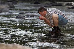 rugged man drinking water from a stream in Upstate New York