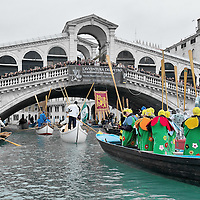 VENICE, ITALY - FEBRUARY 20: Boats from from several rawing association reach Rialto Bridge and sail along the Grand Canal during the Venetian Feast on February 20, 2011 in Venice, Italy. During the Venetian Feast a traditional water parade sails from San Marco along the Canal Grande to the  district of Cannaregio where there the crowd waits for the Svolo della Pantegana  (flight of the mouse).  .