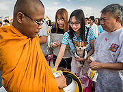 01 JANUARY 2016 - BANGKOK, THAILAND:          A woman with her pet dog makes merit by presenting Buddhist monks with alms during the annual New Year's mass merit making ceremony on at Sanam Luang in Bangkok. The ceremony is sponsored by the Bangkok city government. More than 500 Buddhist monks participated in the ceremony this year. Thais usually go to temples and religious observances to meditate and make merit on New Year's Day.     PHOTO BY JACK KURTZ