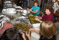 "Bessie Kafanelis, Katherine Dorshimer and Christine and Samantha Kemos prepare ""Dolmathes"" (stuffed grapes leaves) in preparation for the 26th annual Greek Summer Festival to be held Saturday starting at 10 am at the Taxiarchai Greek Orthodox Church in Laconia.  (Karen Bobotas/for the Laconia Daily Sun)"
