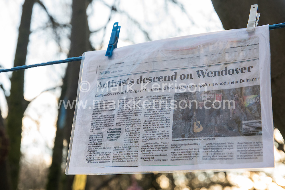 Wendover, UK. 10 January, 2020. A newspaper cutting hangs in the Wendover Active Resistance Camp. Stop HS2 activists from around the UK established the camp in woodland outside Wendover on the proposed route for HS2 through the Chilterns AONB in response to requests for assistance from members of the local community opposed to the high speed rail link. The impact on the immediate area is expected to be even worse than initially expected, with not only two 500m viaducts and a 1km embankment to be constructed but also a Bentonite factory and 240-bed accommodation block.